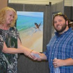 Kerry Baucom with Texas Health Presbyterian Hospital Rockwall presents Greg Lubiani with the Best of Show award of $500.