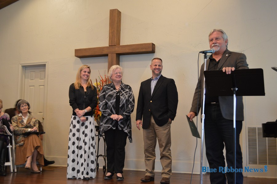 rockwall mayor jim pruitt is joined by members of the smith family as he gives a proclamation in recognition of the rockwall wedding chapels 100 year