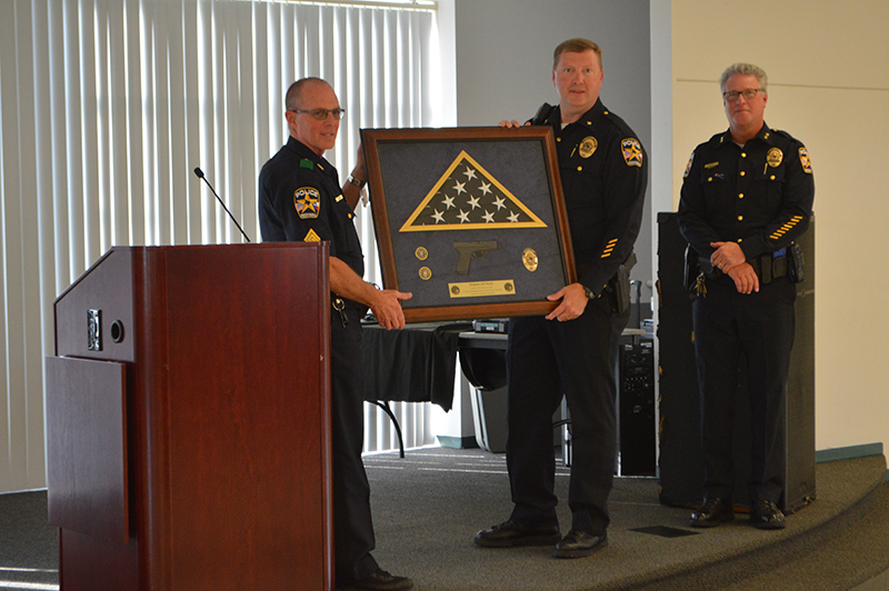 Sergeant Jeff Welch receives a plaque from Rockwall Police Department Chief Kirk Riggs and Assistant Chief Kirk Aldridge.