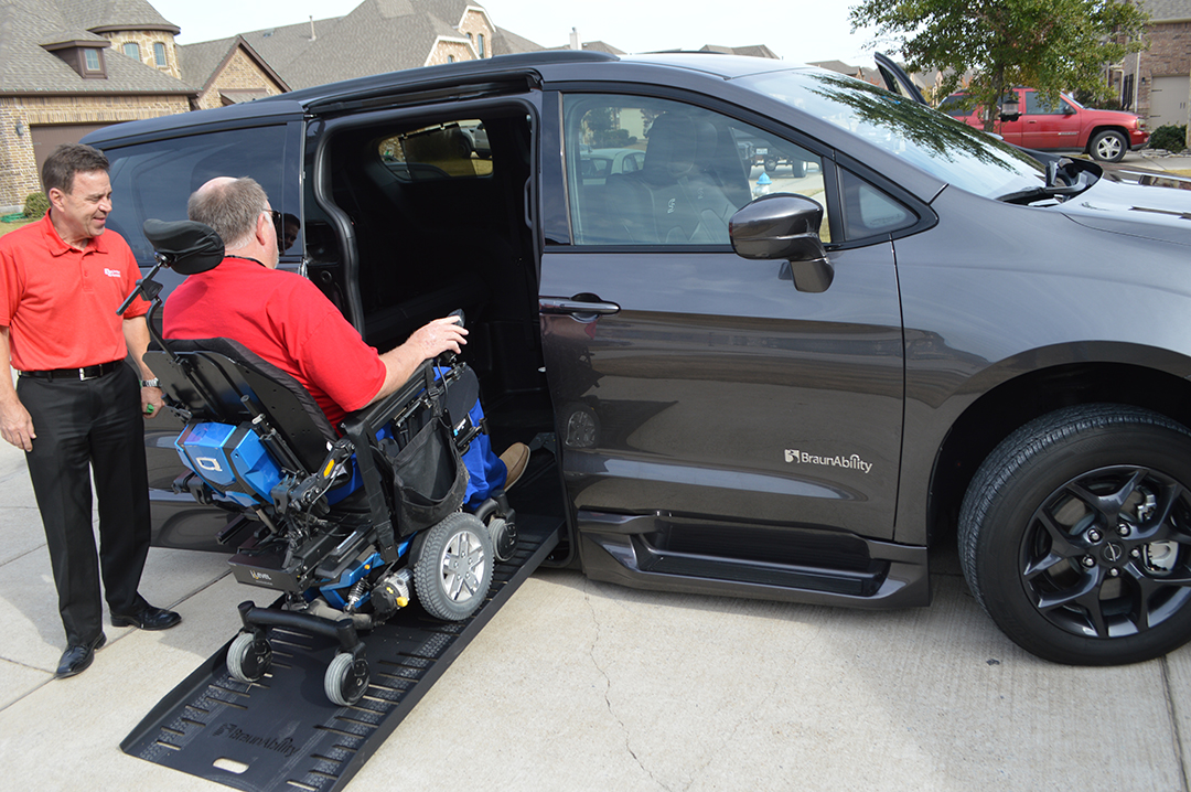 Gary Wilkins rides up the ramp on his new wheelchair-assisted vehicle.
