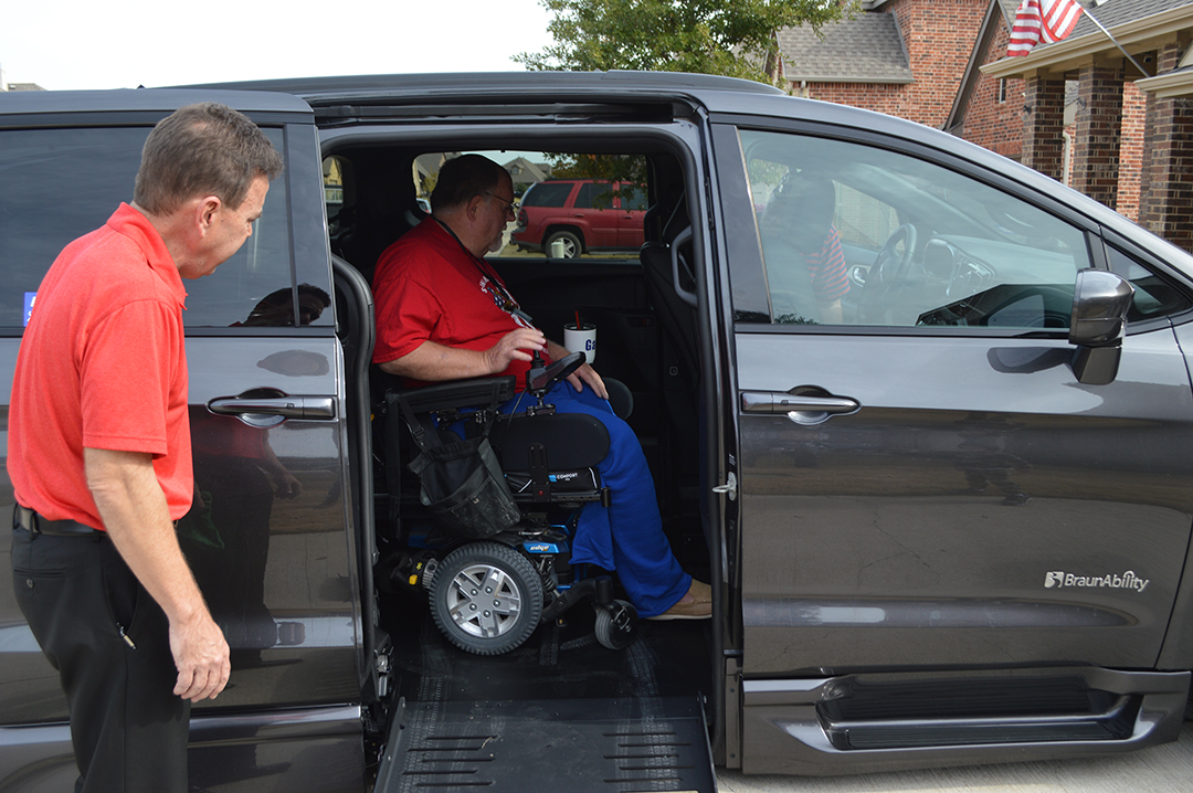 Gary Wilkins locks his wheelchair in place inside his new handicap-accessible vehicle.