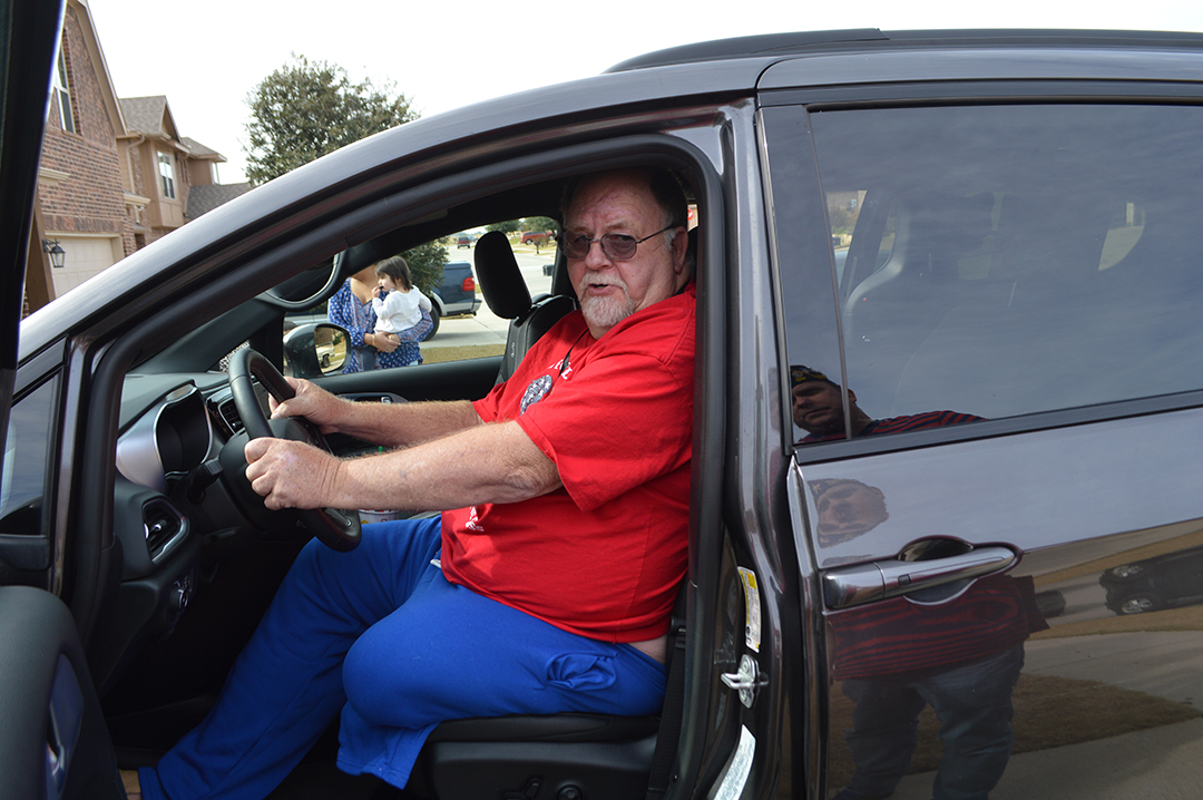Gary Wilkins sits behind the wheel of his new handicap-accessible vehicle.