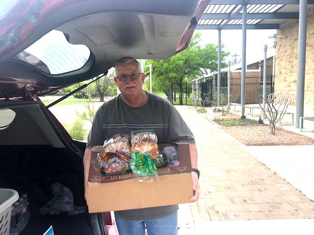 Jim Turner delivers a box full of groceries for Sue to the J.E.R. Chilton YMCA at Rockwall.